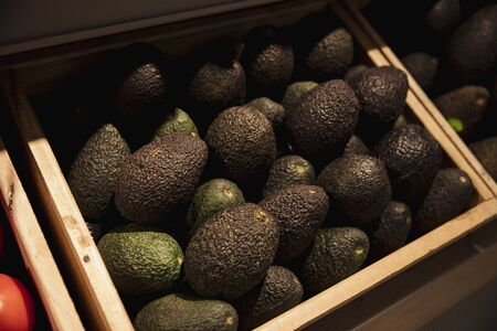 A close-up shot of an abundance of fresh Avocados on display at a market stall.