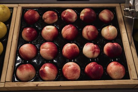 A close-up shot of an abundance of fresh Peaches on display at a market stall.