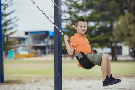 A side-view shot of a young caucasian boy wearing casual clothing, he is having fun on a swing in a public park.