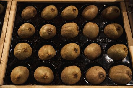 A close-up shot of an abundance of fresh Kiwi on display at a market stall.