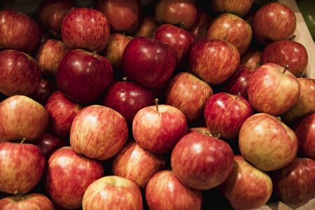 A close-up shot of an abundance of fresh Red Apples on display at a market stall.
