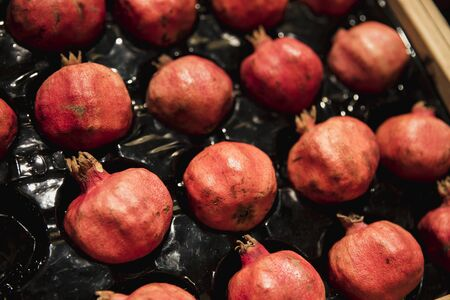 A close-up shot of an abundance of fresh Pomegranate on display at a market stall. Imagens