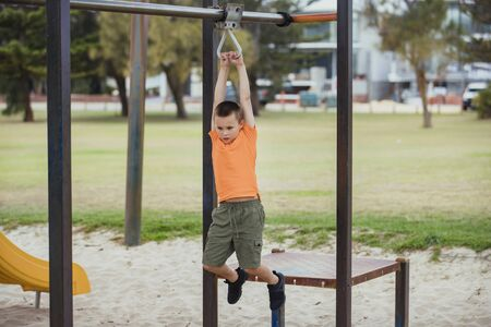 A side-view shot of a young caucasian boy wearing casual clothing, he is swinging from a metal frame in a public park.