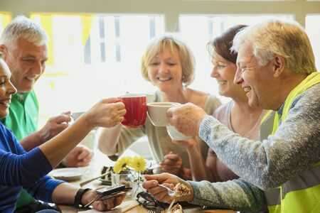 A group of five people taking a break from city cleaning and toasting with their coffees. Stock Photo