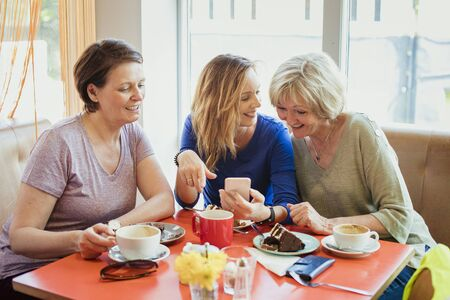 A group of three mature women having coffee and cake; they are looking at one of their phones. Stock Photo