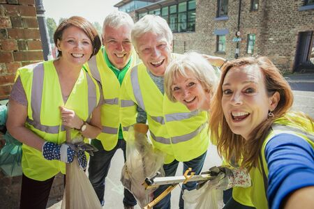 A group of five people taking a selfie. They are wearing high visibility jackets and are participating in a city clean-up. Stock Photo