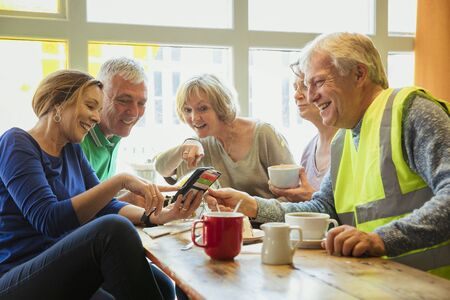 A group of five people taking a break from city cleaning and having coffee and cake; they are looking at one of their phones. Stock Photo