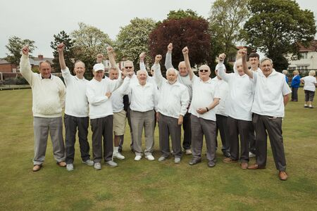 A front view shot of a community of senior men punching the air, celebrating after their lawn bowling game. 版權商用圖片