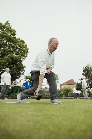 A front view shot of a senior man taking his shot in a game of lawn bowling.