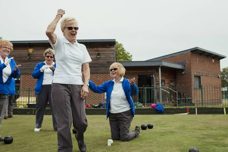 A small group of senior women celebrating during lawn bowling, with one woman punching the air.
