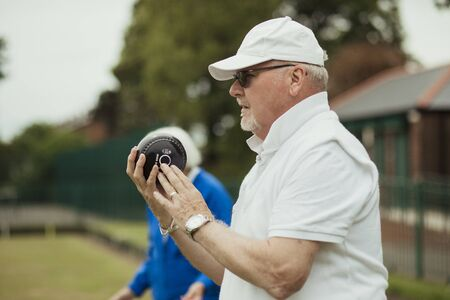 A close up shot of a focused senior man holding a bocce ball, ready to take his shot. He is wearing a white cap and sunglasses.