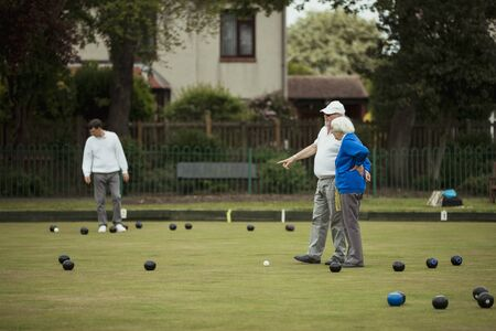 A wide view shot of a senior adult teaching a friend how to play lawn bowling on grass, surrounded by bocce balls. Stock Photo