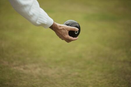 A close up shot of a senior adult holding a bocce ball, ready to take their shot in a lawn bowl game. Stockfoto