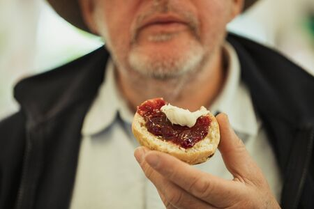 A close up shot of a bitten jam scone, held by a senior man.