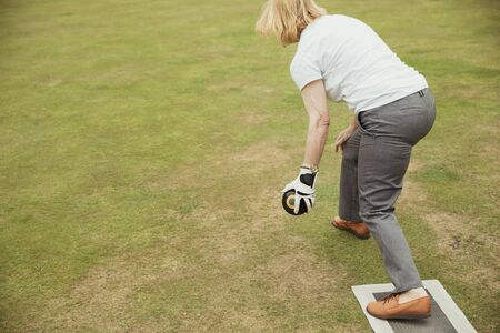A rear view shot of a senior woman holding a bocce ball, ready to take her shot in a lawn bowling game.
