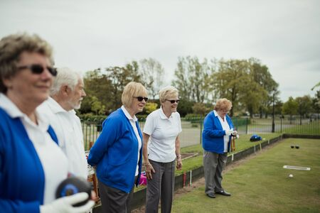 A small group of senior friends watching the lawn bowling game, standing on grass.