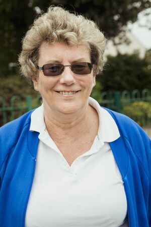 A portrait of a senior woman smiling at a bowling green. She is wearing sunglasses.