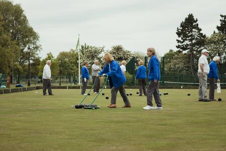 A group of bocce balls being collected by a senior woman using a pick up tool at a bowling green. Stock Photo