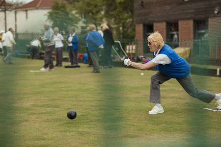 A side view shot of a senior woman taking her shot in a game of lawn bowling. Stock Photo