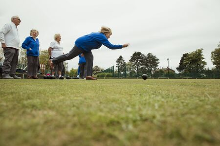 A side view shot of a group of senior friends lawn bowling on grass, with one woman who has taken her shot. 스톡 콘텐츠