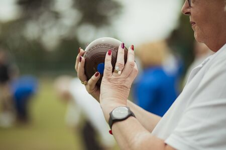 A close up shot of a senior woman holding a bocce ball, ready to take her shot. She is wearing nail polish and a watch.