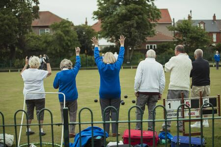 A rear view shot of a group of seniors cheering at a game of lawn bowling.