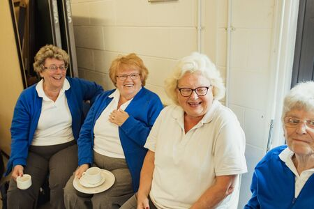 Four senior women sitting together indoors and having coffee. They are smiling and bonding with each other.