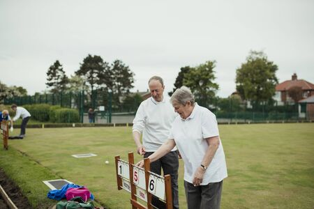 Two seniors at a bowling green setting up the scoreboard. Stockfoto
