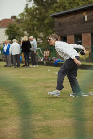 A side view shot of a senior woman taking her shot in a game of lawn bowling. Stockfoto