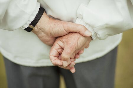 A close up shot of a senior mans hands behind his back, holding them together.
