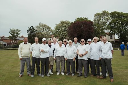 A front view shot of a community of senior men smiling at a bowling green. Imagens