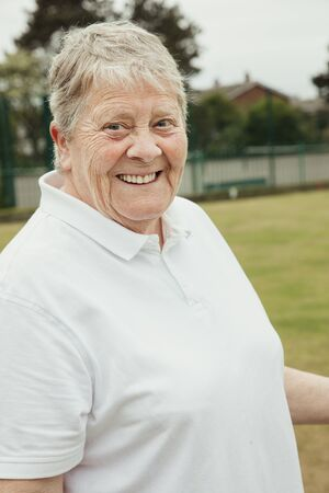 A portrait of a senior woman smiling at a bowling green. Stockfoto