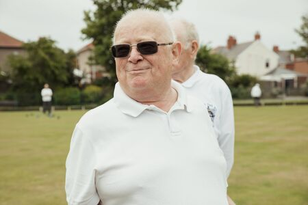 A portrait of a senior man smiling at a bowling green. He is looking away and wearing sunglasses.