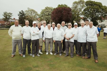 A front view shot of a community of senior men smiling at a bowling green. Stockfoto