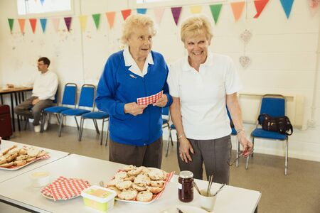 A front view shot of two senior friends selling scones at a bake sale. Stock Photo