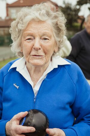 A portrait of a senior woman at a bowling green, holdng a bocce ball. Stockfoto