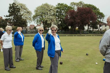 A front view shot of a group of senior women giving their thumbs up at a bowling green. Stockfoto