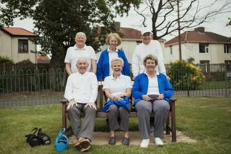 A group of senior adults sitting on a bench at a bowling green, looking at the camera.