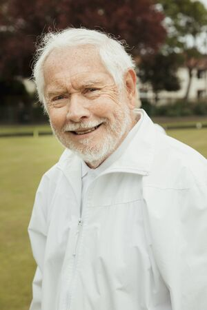 A portrait of a senior man smiling at a bowling green.