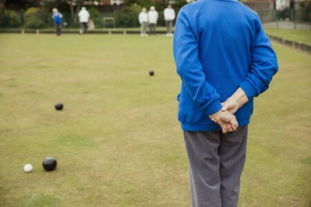 A rear view shot of an unrecognizable person spectating a lawn bowling game, standing with their hands behind their back. Stockfoto