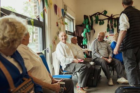 A group of senior adults sitting indoors and bonding with each other.