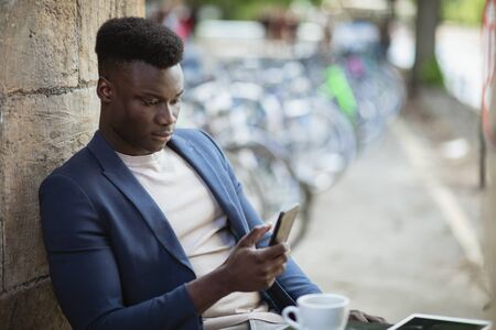 Businessman sitting down at an outdoor table in a city while typing on his mobile phone. Stockfoto