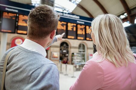 A businessman and businesswoman looking at a departure board in a train station.