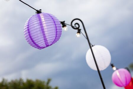 A close-up of paper lanterns hanging up alongside a set of string lights at a garden party.