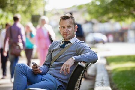 A businessman sitting on a park bench while holding his mobile phone but looking at the camera.