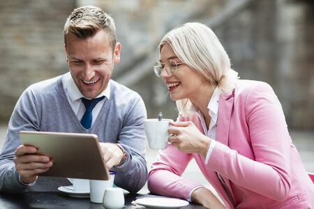 Two businesspeople sitting down and laughing at something on a digital tablet. The businesswoman is holding a hot drink while the businessman holds the tablet. Stockfoto