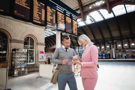 A businessman and businesswoman standing together at a train station. The woman is showing the man something on her mobile phone. Stockfoto