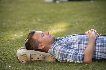 A close-up of a man laying his head on his bag in the park.