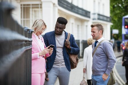 A businesswoman and two businessmen standing together on a city street. The woman is showing one man something on her phone while the other man is looking over them and smiling.