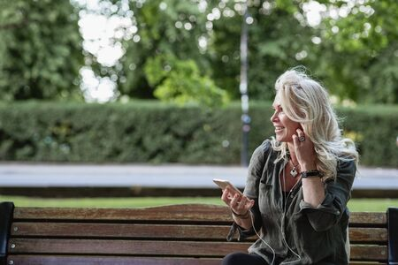 A woman sitting on a park bench listening to music on her MP3 player while looking sideways. Stockfoto